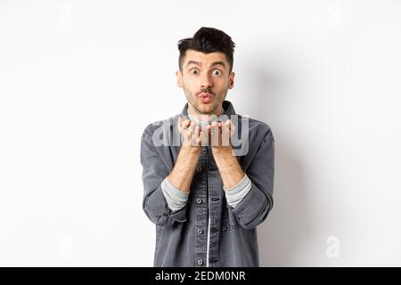 Romantic handsome man blowing air kiss, looking silly at camera, standing in trendy clothes on white background