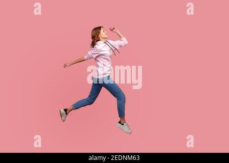 Full length side view of young female in hoodie and jeans running in air, hurrying for discounts, empty copy space for advertising. Indoor studio shot Stock Photo
