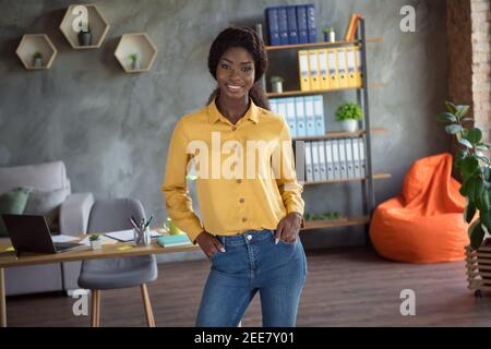 Photo of confident young afro american business woman hold hands pockets wear yellow shirt jeans stand in office indoors