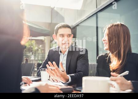 Handsome Asian businessman in a meeting, discussing work with his team and client at a cafe