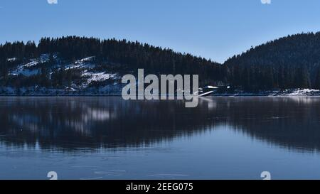 Peaceful view of frozen lake Schluchsee in the Black Forest hills, Germany in winter season with coniferous forest reflected on the ice surface. - Stock Photo