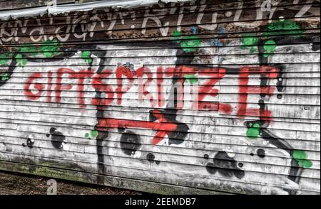 Graffiti von Corona mit dem Schriftzug  ' Giftspritze '   vor dem Impfzentrum in der Arena in Berlin Treptow, , Berlin Stock Photo