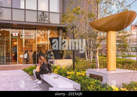 tokyo, japan - january 13 2020: Tourists resting at the Japan Olympic Museum adorned with the replicas of the Olympic Cauldrons of Sapporo Olympic Win - Stock Photo