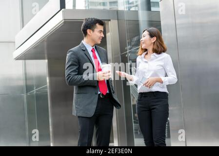 Business colleagues talking while walking in front of office building
