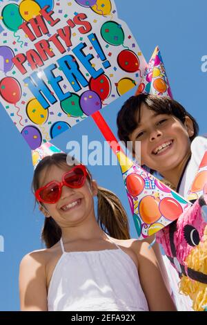Portrait of a girl with her brother wearing birthday hats and smiling