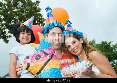 Portrait of a mid adult couple celebrating birthday with their daughter