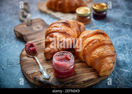 Rustic styling of fresh croissants and fruit jam on the antique wooden board