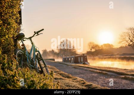 Canal boat with mountain bike left leaning against hedge row early morning sunrise dawn with golden light in sky on the River Trent and mist rising