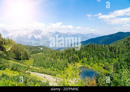 Magical idyllic landscape with lake in mountains in Alps Europe. tourist trail on green hills in Alps. Beautiful rock and admire amazing view to mountain peaks. Fantastic sunny day is in mountain lake