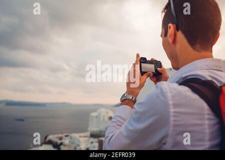 Santorini traveler man taking photo of Caldera from Oia, Greece on camera. Tourism, traveling, summer vacation. Tourist admiring Aegean sea landscape.