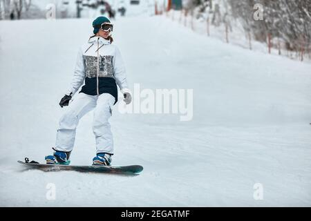 cheerful woman riding on snowboard in the mountains in winter. woman in white ski suit. - Stock Photo