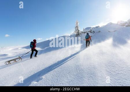 Mother and son towing a sled uphill in the snow - Stock Photo