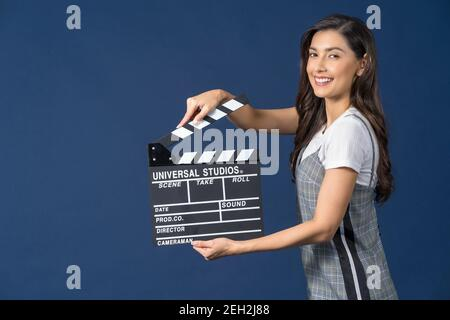 Happy young Asian woman holding movie clapperboard on studio setup film on blue color background, broadcast and producer, cinema and movie cut concept