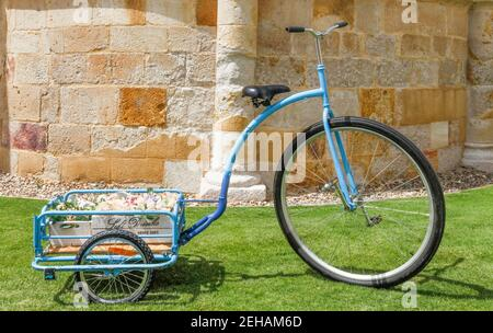 Floral decoration for celebrating an outdoor party with a bicycle, vintage blue tricycle in the garden.
