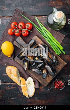 Mussels stew in white wine and herbs, on wooden cutting board, on old dark wooden table background, top view flat lay
