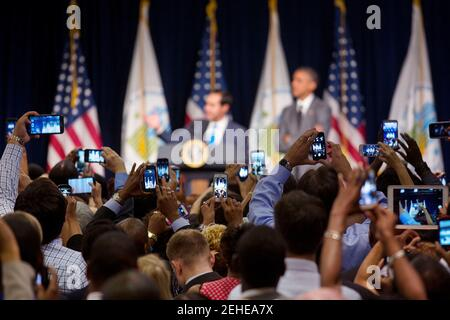 Audience members photograph HUD Secretary Julián Castro introducing President Barack Obama at the Department of Housing and Urban Development in Washington, D.C., July 31, 2014. - Stock Photo