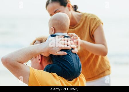 Happy family on the beach.  Father, mother and baby having fun on summer vacation. Holiday travel concept