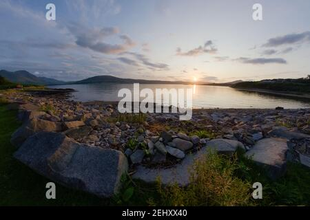 A rocky boulder sea shore at sunset. Looking west near East Suisnish on the Isle of Raasay, isle of skye in the distance. A fish eye perspective.
