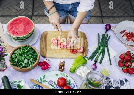 Preparing food on table outdoors. Woman cutting red tomato with kitchen knife on wooden board. Top view
