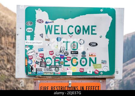 Stickers on a welcome to Oregon sign, Wallowa County, Oregon. - Stock Photo