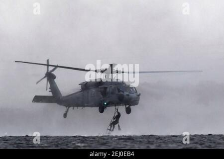 U.S. Air Force Special Tactics teams assigned to the 24th Special Operations Wing, conduct hoist operations with a Navy MH-60 Seahawk helicopter during Emerald Warrior at Hurlburt Field February 18, 2021 in Mary Esther, Florida.