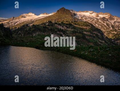 ENG: Aneto summit and the Maladeta massif viewed from Ibón Superior de Villamuerta in a summer sunrise (Benasque valley, Pyrenees, Spain) ESP:  Cumbre Stock Photo