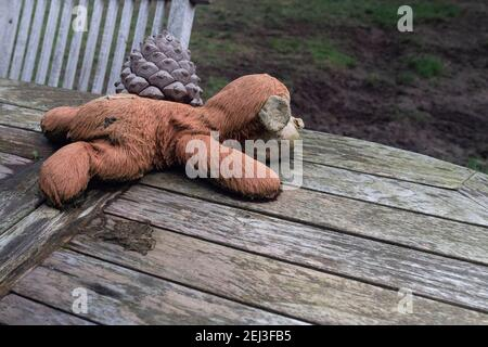 Old weathered and wet plush toy lies on a table next to a pine cone