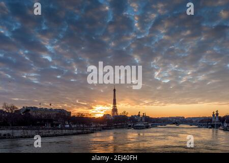 Paris, France - February 12, 2021: CItyscape of Paris in winter. Ships and brigde over Seine river with Eiffel tower in background and dramatic cloudy