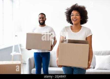 Joyful Black Spouses Carrying Moving Boxes Entering New Home Together