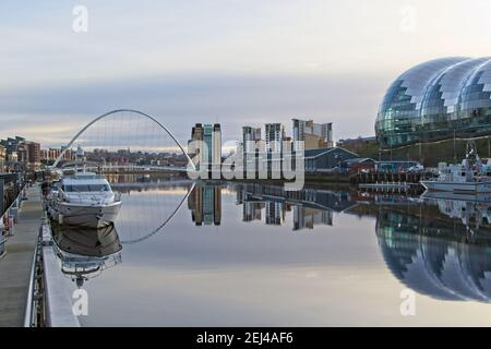 Looking down the River Tyne towards the Gateshead Millennium Bridge and Gateshead Quays with beautiful reflections in the very still water. - Stock Photo
