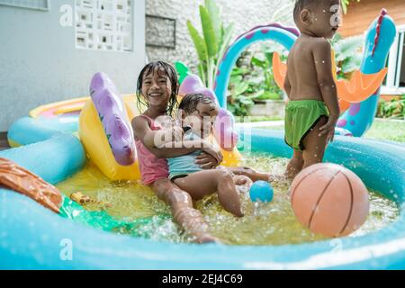 big sister smiles hugging younger sister while playing together in rubber pool portable at home - Stock Photo
