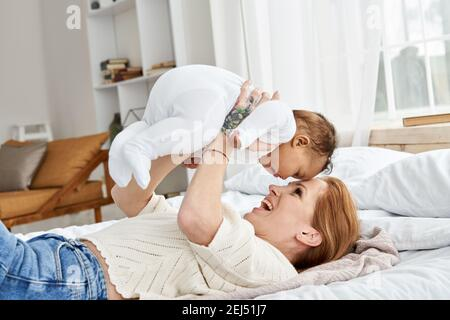 Happy caucasian mother having fun lifting cute little baby daughter in bed.
