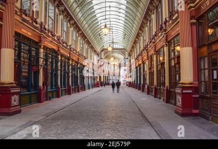 A couple walk past closed shops at Leadenhall Market during the coronavirus lockdown. London, United Kingdom February 2021.