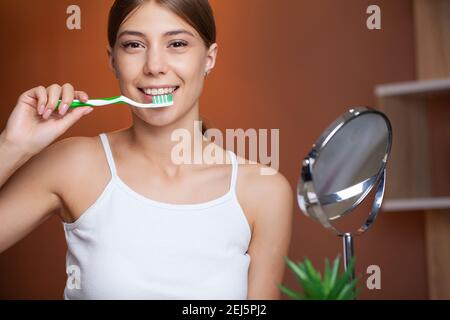 Beautiful Smiling Woman Brushing Healthy White Teeth With Brush.
