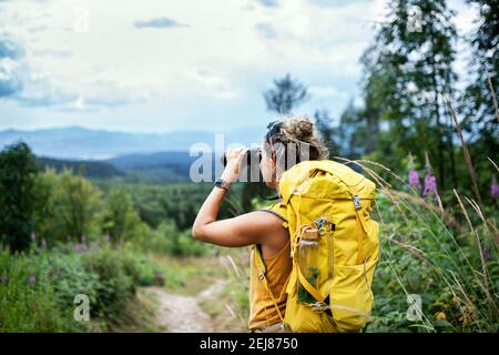 Rear view of woman hiker with backpack on a hiking trip in nature, using binoculars. - Stock Photo
