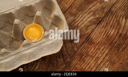 One broken egg in a cardboard egg tray. Half egg with yolk in an empty box on wooden background