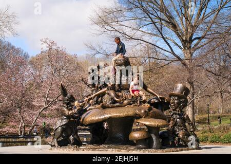 Children playing on the Alice in Wonderland bronze sculpture by José de Creeft in Central Park, NYC, New York, America, USA