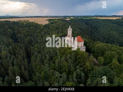Aerial view of a medieval castle, Kokorin. Fortified palace with a tower and a wall standing on a hill covered by trees.Tourist spot. Castles in the C