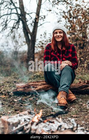 Happy traveler girl in hipster clothes sits on a log in the forest near the fire by camping. Woman enjoying relaxing in the forest