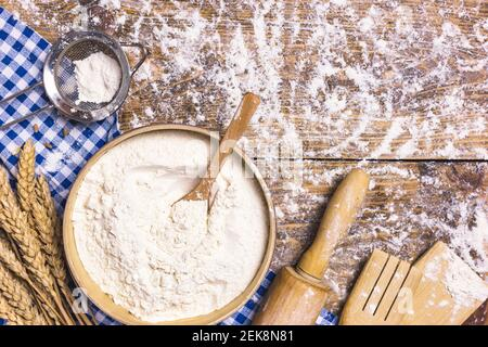 Frame of baking and cooking pastry or cake with ingredients and utensils. Flour and wheat on rustic wooden background with copy space for text, flat l