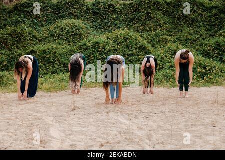 Women with yoga instructor practicing Uttanasana on sand against plants