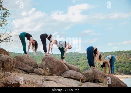 Young women with instructor practicing Uttanasana yoga on rock