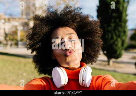 Young woman with eyes closed puckering while taking selfie at park