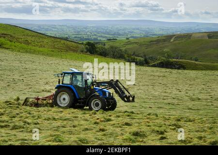 Tractor haymaking (pulling & towing tedder, tedding farm silage crop) in scenic farmland pasture field near Grassington, Yorkshire Dales, England, UK.