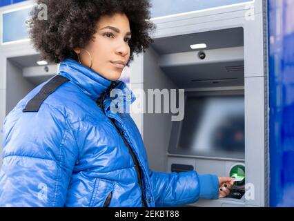 Afro woman removing ticket from ticket machine while standing bus stop - Stock Photo
