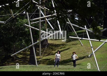 "Two people stop to look at ""Free Ride Home"" (by artist Kenneth Snelson) during their visit to the Storm King Art Center in Mountainville, New York, August 8, 2020. Located in the Hudson Valley, Storm King Art Center sits on 500 acres and is home to one of the largest collections of contemporary outdoor sculptures in the United States. (Anthony Behar/Sipa USA) Stock Photo"
