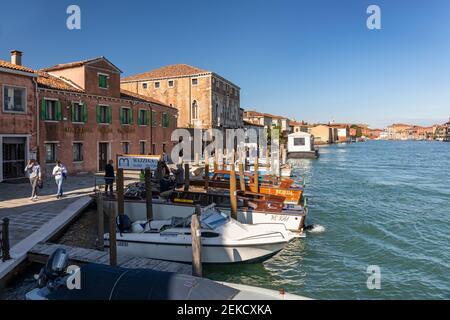 Mazzega Glass Factory and tourists walking along the street beside The Canal Grande di Murano, Murano Venice