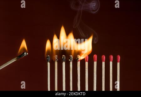 Lit match next to a row of lighting matches. Red phosphorus matches on dark red background. Concept of ignition or initiation