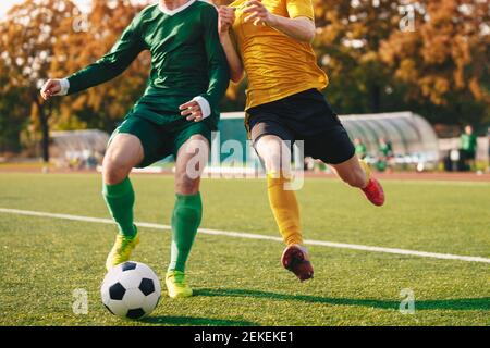 Two Footballers Running and Kicking Game. Adult Football Players Compete in Soccer Match. Soccer Bench and Substitute Players in the Blurred Backgroun - Stock Photo