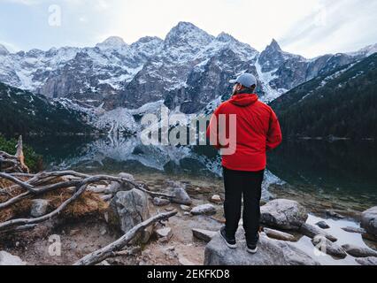 Man near Sea Eye Lake (Morskie Oko) in spring. Tatra National Park, Poland - Stock Photo